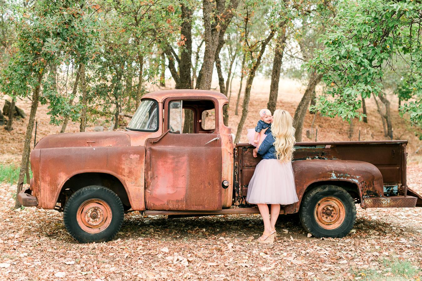Mom and baby girl and old rustic ford truck