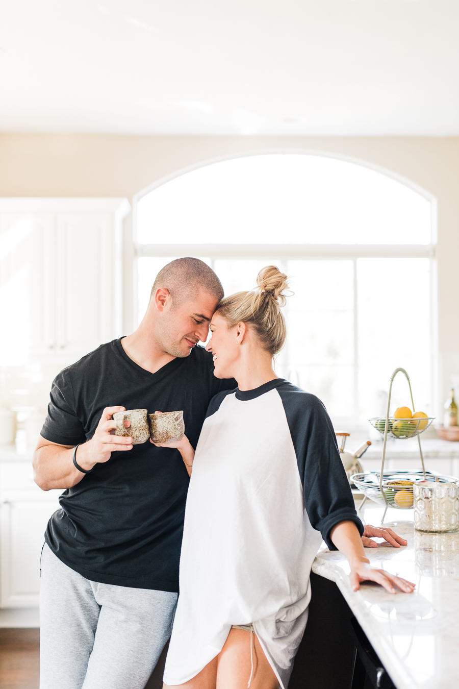 couple drinking coffee in kitchen looking cozy