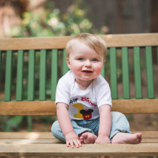 little guy sitting on bench for one year photos