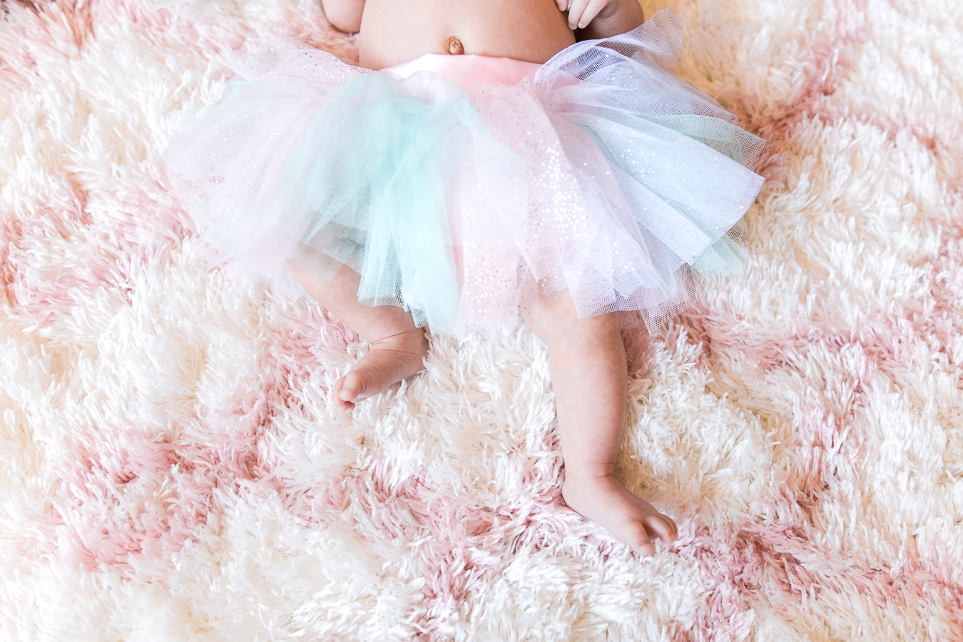 Newborn girl wearing pink and mint tutu with little toes showing