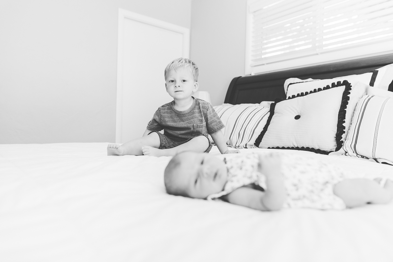 black and white photo of baby girl laying on bed with big brother in focus in the background.