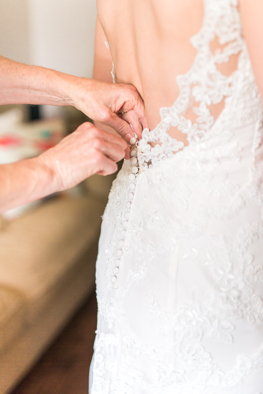 mom butting up back of wedding dress