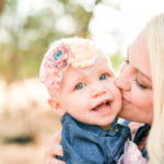 Mom kissing baby girls cheek